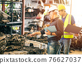 Engineer employee working with manager checking stock inventory in garage used engine car part store 76627037