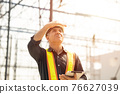Foreman builder engineer worker looking at large building construction site sunny day hard work. 76627039