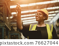 Black African professional women worker happy working count checking inventory production stock control in business factory  industry warehouse waring engineer suit and helmet for safety 76627044