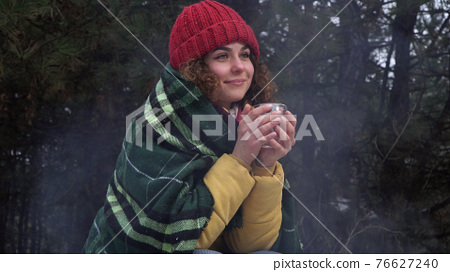Young woman drinks tea by the fire in the winter forest 76627240