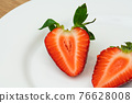 Red ripe strawberry slice on white plate 76628008
