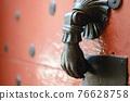 Ancient metal knocker on a wooden door 76628758