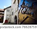 Ancient metal knocker on a wooden door 76628759