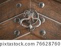 Ancient metal knocker on a wooden door 76628760