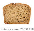 Slice of fresh dark rye bread, from above. Brown colored sourdough bread, a mix of rye grain flour, leaven and spices, crusty baked in an oven. Staple food. Isolated, over white, close-up, food photo. 76630210
