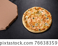 Tasty fresh oven pizza with tomatoes, cheese and mushrooms on a dark concrete background 76638359