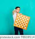 Cute kid holding a game of chess in his arms, studio shooting 76639514