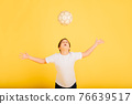 Cute boy is holding a football ball made of genuine leather isolated on a yellow background. Soccer 76639517