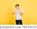 Cute boy is holding a football ball made of genuine leather isolated on a yellow background. Soccer 76639519