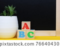 ABC blocks next to a blackboard and a potted houseplant. Back to school. English for beginners. Empty space for text. 76640430