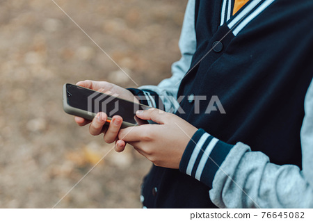 Child hands uses smartphone in summer park, looking at screen of devices outside 76645082
