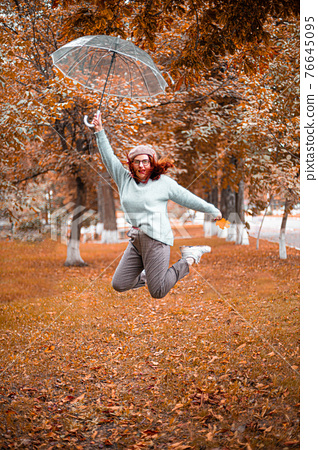 Cheerful Caucasian girl jumping up with a transparent umbrella in the autumn park. 76645095