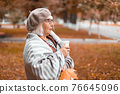 A lady in a warm wool blanket holds a paper cup of hot tea or coffee drink while enjoying the beautiful view in the fall season 76645096