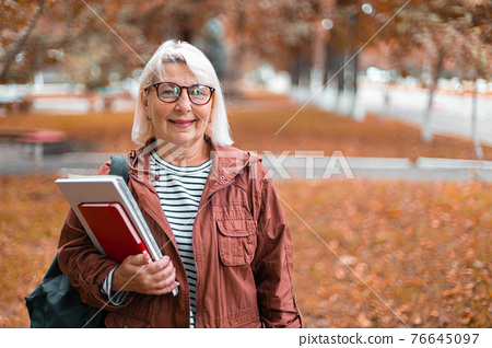 Smiling woman in casual clothes stands holding notebooks and backpack in city street. 76645097