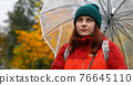 Young girl in warm clothes with a transparent umbrella and backpack on her back outside in cold weather after rain. Woman looks at the camera. 76645110