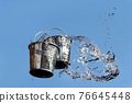 A falling buckets splashes water, on a background of blue sky. 76645448