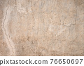 Grunge gray background of cracked peeling walls with peeled putty in beige tones. 76650697