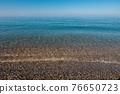calm clear sea, pebble shore, flat horizon 76650723