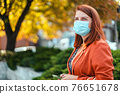 Businesswoman with safety mask standing in the city. Beautiful young girl with red hair in a protective medical mask against allegria, virus 76651678
