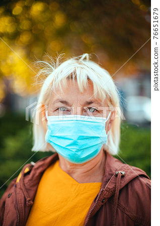 Caucasian adult blond woman 50 years old in bright robe and protective medical respirator mask looking away on the park 76651679