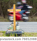 A roadside memorial cross with a candles commemorating the tragic death,on background ride motorbike 76652088