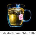 A tea bag with label fall into a glass mug with hot water,  on a black background 76652102