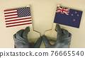 Holding flags of the USA and New Zealand made of recycled paper on the cardboard table, top-down view 76665540