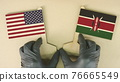 Holding flags of the USA and Kenya made of recycled paper on the cardboard table 76665549
