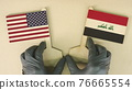 Holding flags of the USA and Iraq made of recycled paper on the cardboard table 76665554