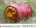 rusty old barrel in a grass 76687853