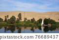 Egypt Nile river side view felucca boat and telephone signal tower 76689437