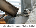 Concrete is poured from a concrete mixer into container on construction site. 76691461