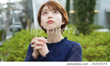 A woman looking up at the sky and praying 76704979