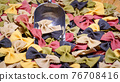 Colored Farfalle Pasta bow tie pasta background. 76708416