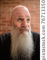 Portrait of happy mature man smiling and thinking with long gray beard 76713350