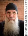 Portrait of mature man with long gray beard 76713364