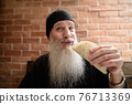 Man smiling with long gray beard while holding taco at restaurant 76713369