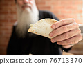 Hand of mature man with long gray beard holding taco 76713370