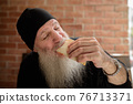 Portrait of happy mature man with long gray beard eating taco 76713371