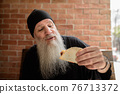 Portrait of mature man with long gray beard holding taco 76713372