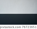 Dark horizontal table surface adjacent to the white wall 76723651