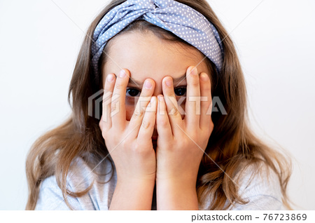 scared child hide and seek game cute girl peekaboo 76723869