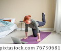 Woman performing sports exercise on online 76730681
