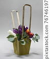 Bouquet of tulips in a decorative paper basket on a white background 76746197