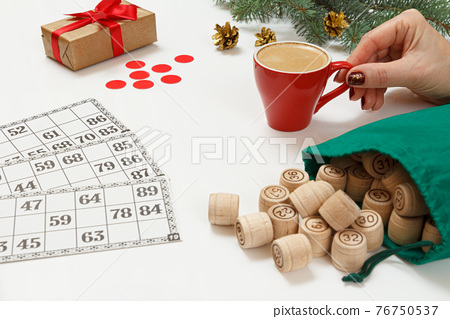 Woman's hand holding a cup of coffee with wooden barrels for a game in lotto 76750537