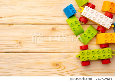 Toy constructor details on wooden background close up 76752984