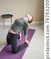 Woman bent back doing yoga asana. Yoga exercise at 76763200