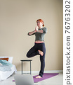 Red hair woman doing yoga asanas. Yoga exercise 76763202