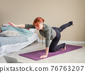 Young woman with red hair performing yoga poses 76763207
