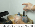 Man puts black ink in a printer using a syringe, hands in gloves closeup. 76769783